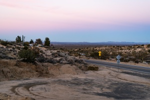 Pastel pink and blue line the desert sky with a road crossing from right to left